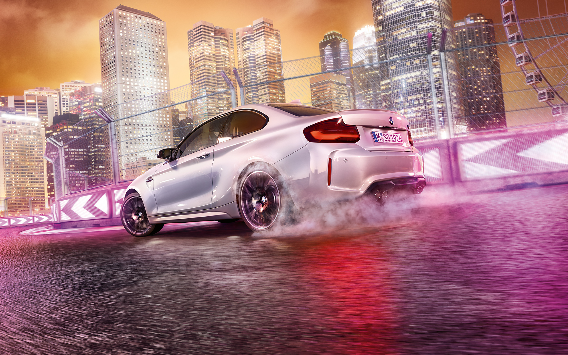White BMW M2 Competition drifting on race track in front of  nocturnal skyline.