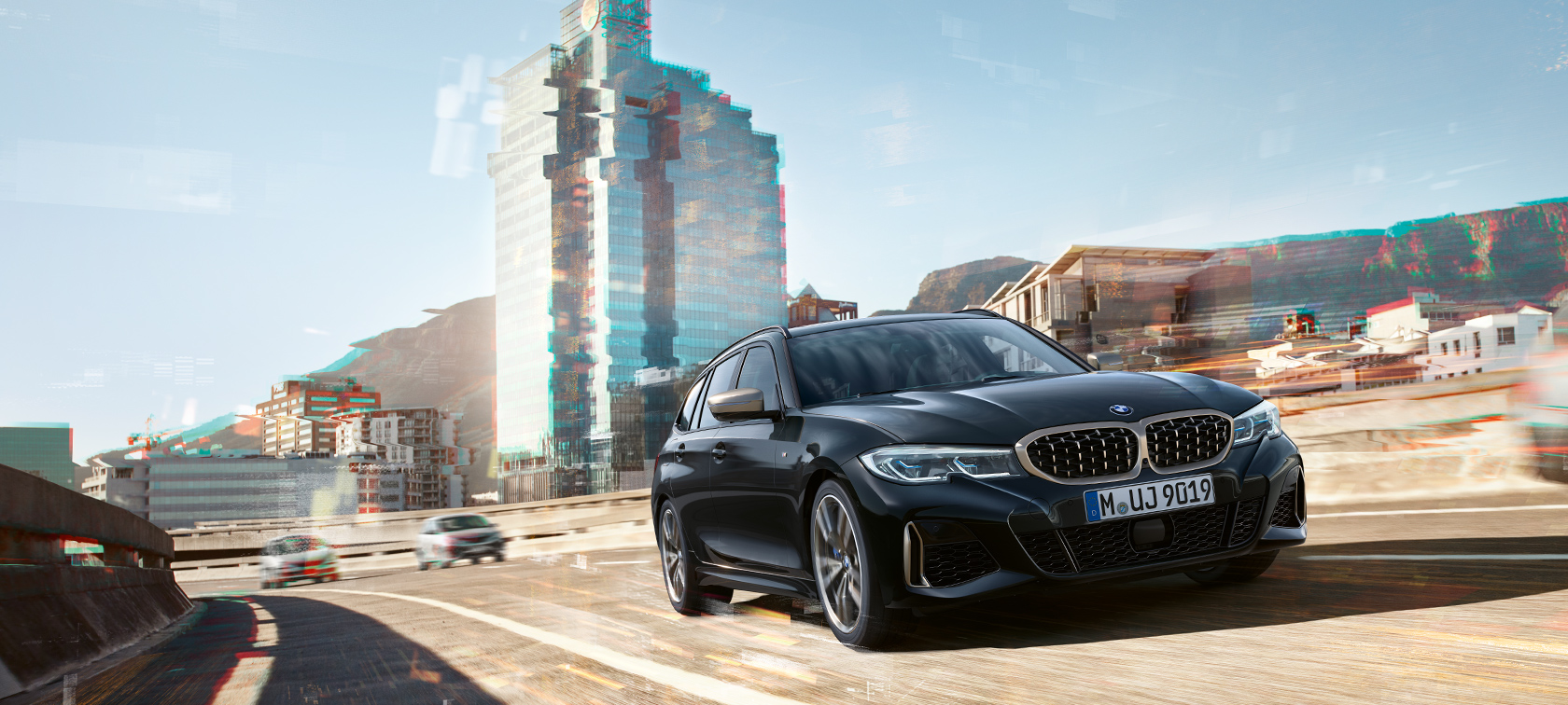 BMW M340i xDrive Touring, Three-quarter front shot driving in front of an urban backround