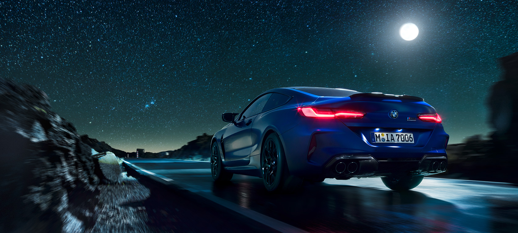 BMW M8 Competition Coupé, rear view, driving at night with full moon.