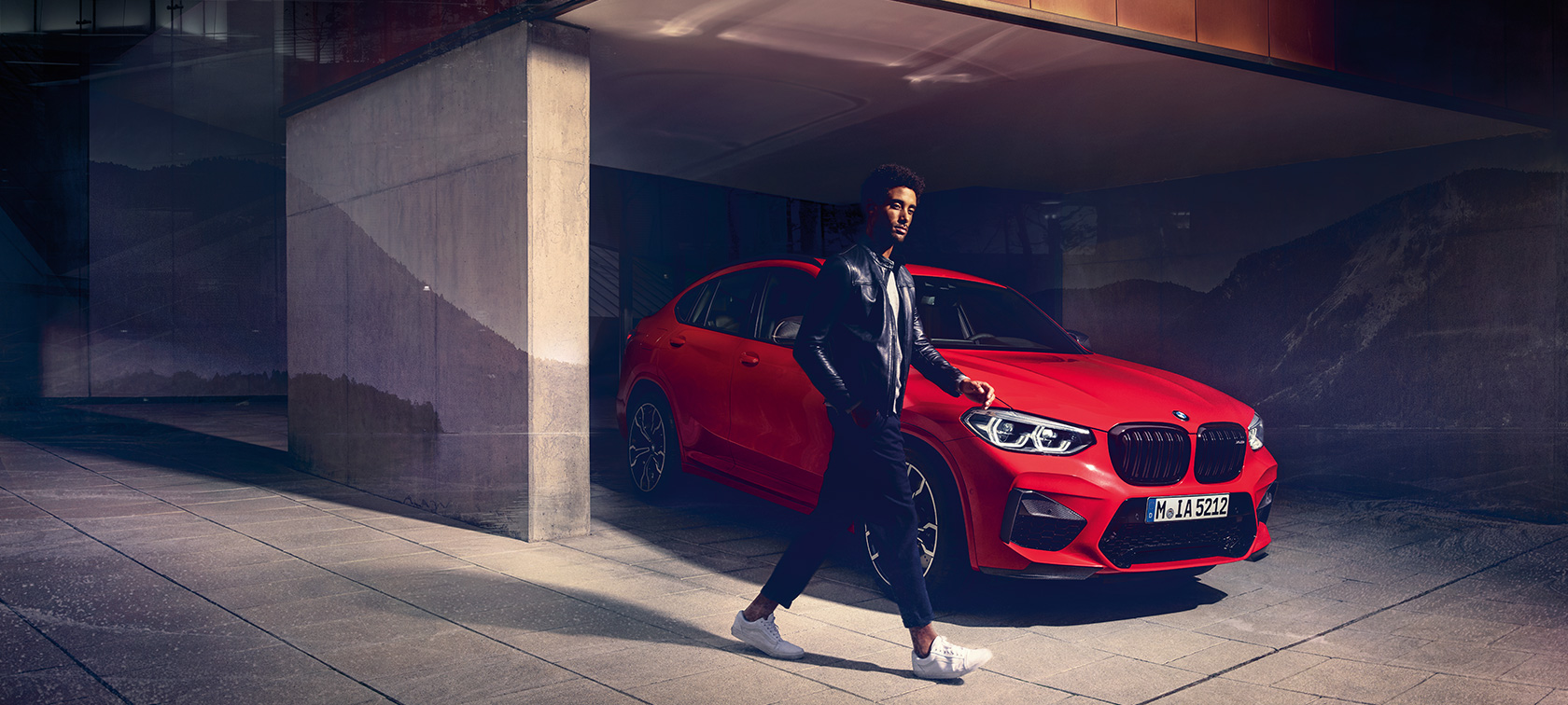 BMW X4 M Competition in Toronto Red metallic, exterior, three-quarter side view with young man.