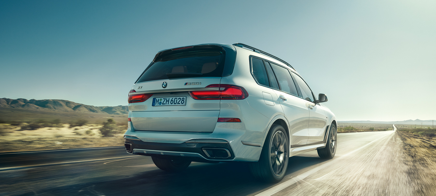 BMW X7 M50i in Mineral White, driving on an empty highway, rear view, G07, 2019