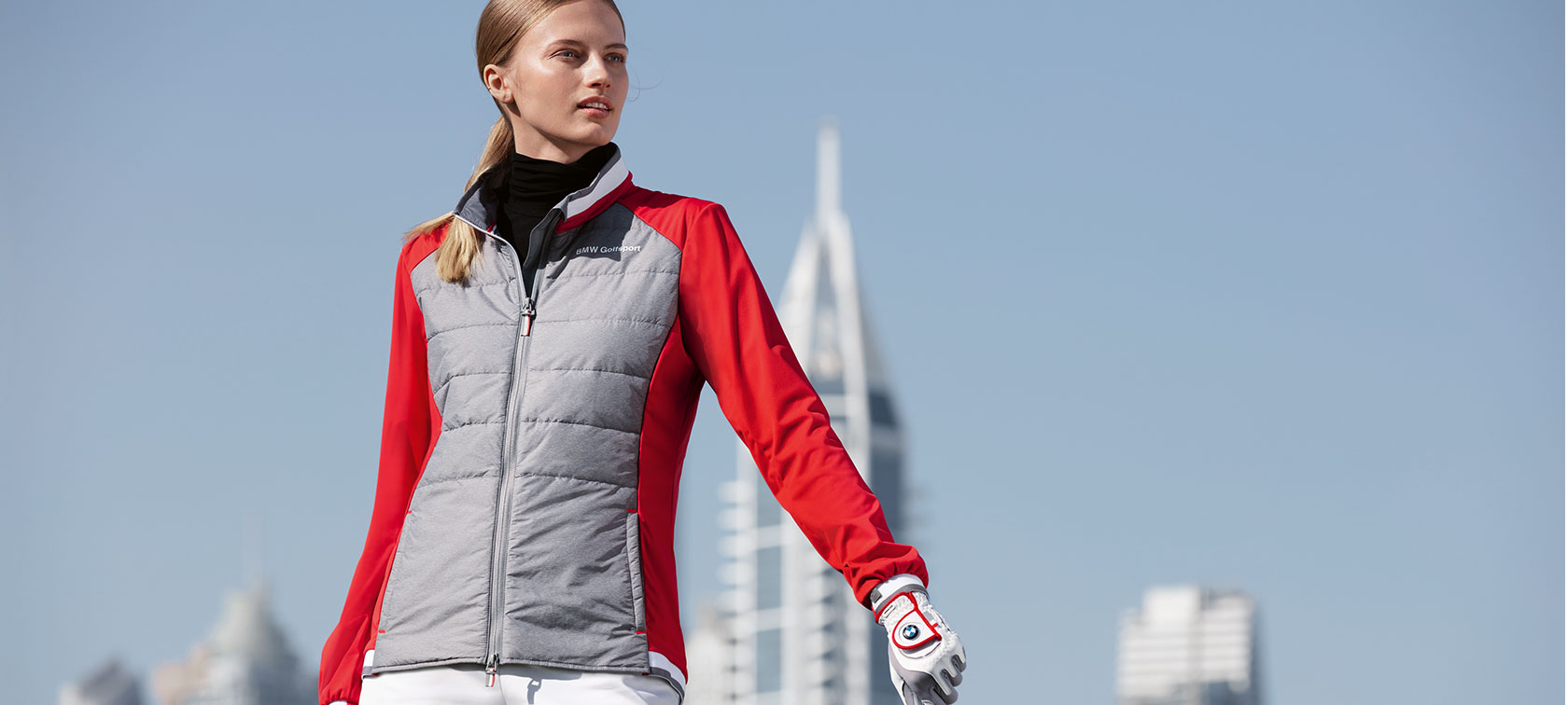 The young woman in the picture presents premium articles from the BMW Golfsport Collection against the backdrop of a big city skyline.